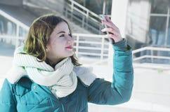 在做selfie的商业中心附近的一个少妇在冬天 免版税库存照片