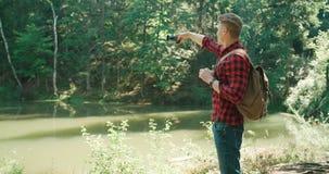 在做selfie的绿色自然的英俊的人由电话 库存图片