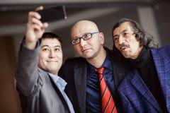 在做selfie的衣服的商人户内,成熟 三个人企业队  现代技术,社会网络 免版税库存照片