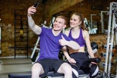 在做selfie的运动服的美好的愉快的夫妇使用智能手机 免版税库存图片