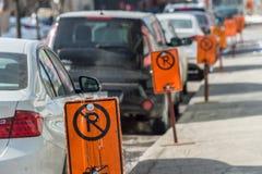 在停放的汽车旁边的禁止停车标志 免版税库存照片