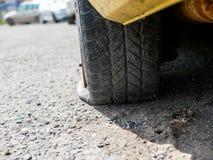 在停放的汽车,浅景深的泄了气的轮胎 免版税库存照片