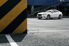 在停放的白色汽车逗留在白天的城市大厦附近 免版税库存照片