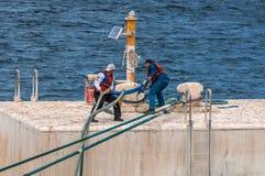 在停泊的平台上工作者熔铸停泊缆绳 免版税库存照片