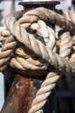 在停泊系船柱附近被包裹的一条重绳索 免版税库存图片