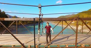 在停留横跨吊桥的年轻人游人的空中飞行 股票录像