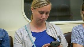 在停留的地铁的一个中年妇女神色智能手机醒 疲乏的妇女 股票录像