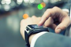 在停车场使用他巧妙的手表的一个人 特写镜头手 免版税库存照片