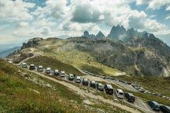 在停车场的停放的汽车在瑞士山中的牧人小屋Rifugio Lavaredo,奥龙佐迪卡多雷, Provincie贝卢诺,意大利下 免版税库存照片