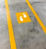 在停车处大厦的走道车道 被绘的黄色脚步betwe 免版税图库摄影