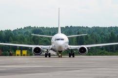 在停车处的乘客飞机在有今后鼻子的机场 免版税库存图片
