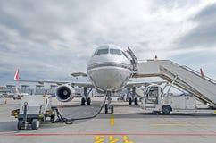 在停车处的乘客飞机在有向前的鼻子和通道的机场 库存图片