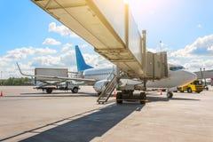 在停车处的商业乘客飞机在机场与和通道 服务和准备的飞行 图库摄影
