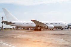 在停车处的白色大飞机在机场 免版税库存照片