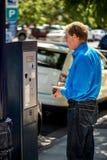 在停车时间计时器前面的人 免版税图库摄影