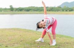 在健康公园的愉快的女孩锻炼 免版税库存图片
