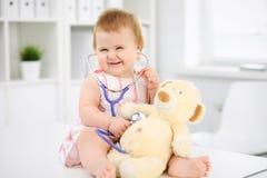 在健康检查以后的愉快的逗人喜爱的婴孩在医生` s办公室 医学和医疗保健概念 免版税库存图片