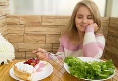 在健康沙拉和蛋糕之间的选择节食食物 库存图片