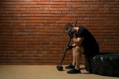 在健身会议以后的人,谈话在电话,当坐橡胶轮子反对砖墙背景时 库存图片
