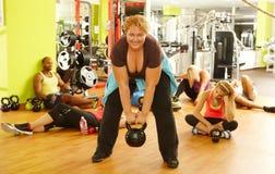 在健身俱乐部的坚定的肥胖妇女训练 库存照片