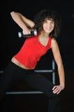 在健身俱乐部的少妇锻炼与哑铃 免版税库存照片