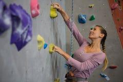在健身俱乐部的微笑的运动员上升的墙壁 免版税图库摄影