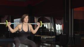 在健身健身房年轻美丽的妇女蹲与在训练的一个酒吧 股票录像