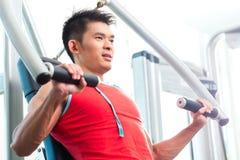 在健身健身房的中国人训练力量 库存照片