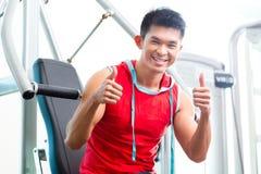 在健身健身房的中国人训练力量 免版税库存照片