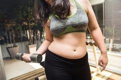 在健身健身房的肥胖妇女减重举的哑铃 免版税库存照片
