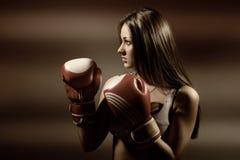 在健身和拳击期间的年轻美丽的妇女 免版税库存照片