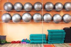 在健身和有氧运动屋子、fitballs和哑铃,背景的运动器材 免版税库存图片