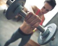 在健身妇女举的哑铃的特写镜头在顶楼健身房 免版税库存图片