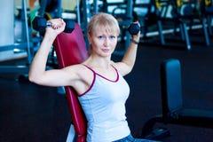 在健身妇女锻炼的特写镜头与哑铃 健身妇女桔子哑铃 免版税库存图片