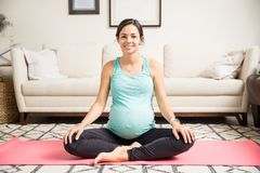 在健身席子的微笑的孕妇开会盘的腿 库存图片
