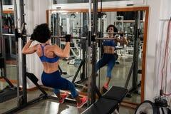 在健身房严重行使的后面妇女使用multipower 库存照片