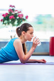 在健身房健康概念的少妇饮用水 免版税库存照片
