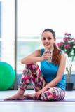 在健身房健康概念的少妇饮用水 免版税库存图片