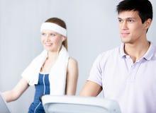 在健身房培训的妇女培训与在健身房的教练 免版税库存图片