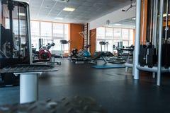 在健身房屋子的不同的训练器材 库存照片