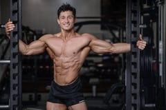 在健身房性感的人推力哑铃的英俊的爱好健美者训练 免版税库存图片