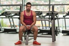 在健身房放松的有吸引力年轻人休息 免版税库存照片