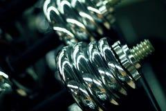在健身房特写镜头照片的哑铃 发光的金属哑铃或杠铃重量 免版税图库摄影