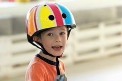 头戴在健身房的一个愉快和疲乏的男孩的画象一件五颜六色的盔甲,当训练时 免版税库存图片