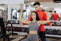 在健身房的一件少女佩带的运动服执行哑铃锻炼,教练帮助她 免版税图库摄影