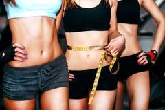 在健身房的三个女孩锻炼 免版税库存图片