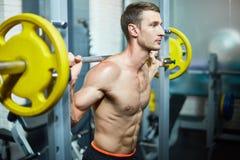 在健身房的举的杠铃 库存照片