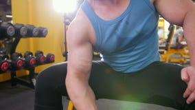 在健身房的举重-年轻肌肉人执行二头肌的训练与哑铃-接近  股票录像