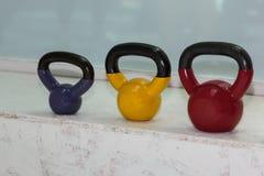 在健身房的五颜六色的哑铃:重量健身设备 图库摄影