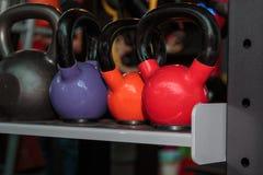 在健身房的五颜六色的哑铃:重量健身设备 库存照片